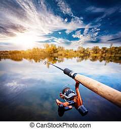 Fishing rod near beautiful pond with cloudly sky - Fishing...