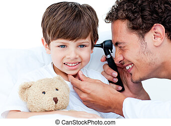 Attractive doctor examining patient\'s ears at the hospital