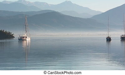 Anchored yachts at misty morning on the lake on mountains...