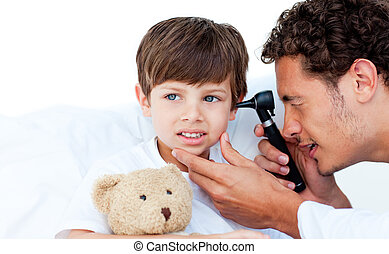 Concentrated doctor examining patients ears at the hospital...