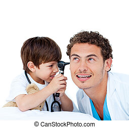 Smiling little boy playing with the doctor against a white...