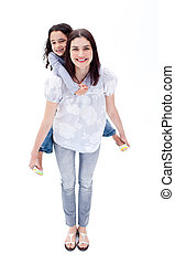 Attentive mother giving her daughter piggyback ride against...