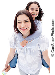Close-up of mother giving her daughter piggyback ride...