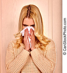 Young woman wisneezes in handkerchief having cold. - Young...
