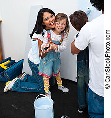 Portrait of little girl painting with her mother