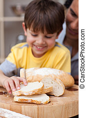 Adorable little boy and his father cutting bread