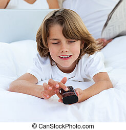 Pensive boy holding a remote control lying on the bed