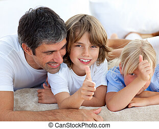 Affectionate father with his children having fun lying on a...