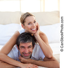 Portrait of a smiling couple lying on the bed