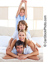 Jolly family having fun in the bedroom