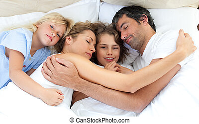 Affectionate family hugging lying in the bed at home