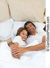 Adorable son with his father lying in the bed