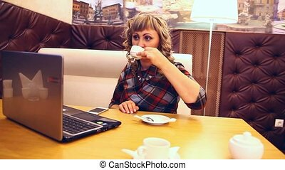 average age of woman thick drinking coffee in a cafe working at a laptop freelancer lifestyle