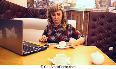 average age of woman thick drinking coffee in cafe working at a laptop freelancer lifestyle
