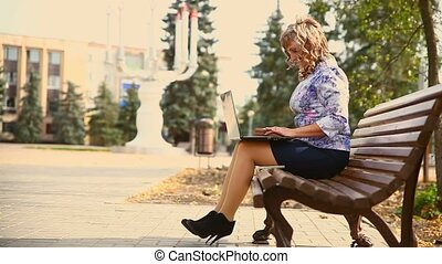 middle-aged woman full of fat sitting on a park bench...