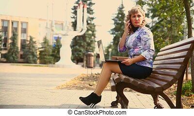 middle-aged woman full of fat sitting on park bench working at a laptop freelancer distant work business wind