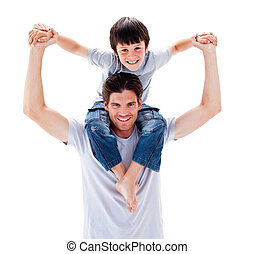 Charismatic father giving his son piggyback ride against a...