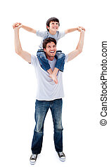 Jolly father giving his son piggyback ride against a white...