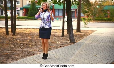 full fat middle-aged on phone woman in the park behind the cars drive lifestyle