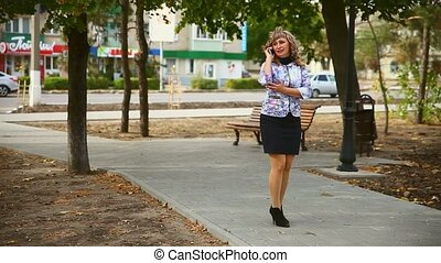 full fat middle-aged on phone in the park woman behind the...