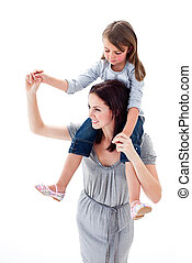 Merry mother giving her daughter piggyback ride against a...