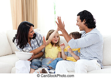 Happy siblings watching TV with their parents in the living...