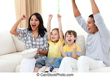 Adorable siblings watching TV with their parents in the...