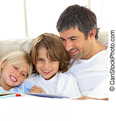 Close-up of father and his children reading book lying in...