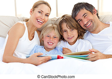 Smiling family reading a book on bed - Smiling family...