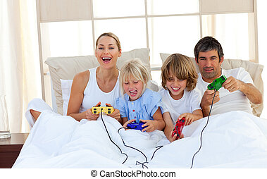 Smiling family playing video game lying on bed