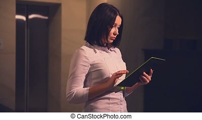 Young woman business hotel manager in an elevator with tablet pc