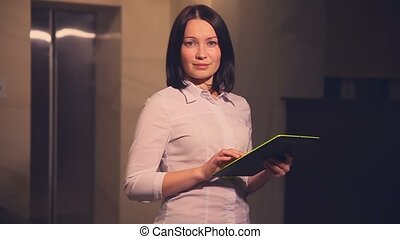 Young business woman hotel manager in an elevator with tablet pc