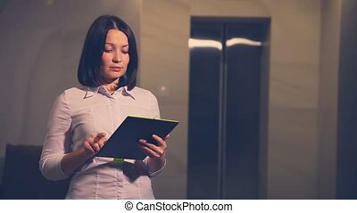 Young woman business hotel manager in an elevator with a Tablet PC