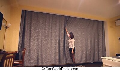 Rear view of a young woman employee of the administrator opens the curtains at the window for the opening of a hotel room