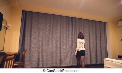 Rear view of a young woman employee of administrator opens...