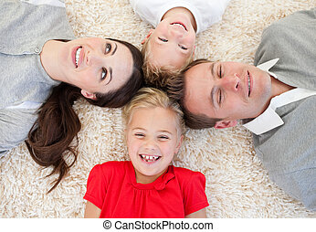 Smiling family relaxing lying on a floor