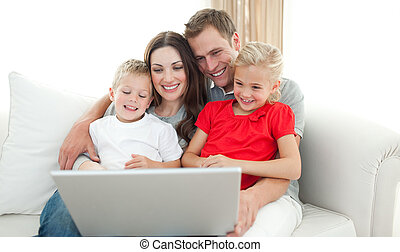 Joyful family using a computer sitting on sofa in the living...