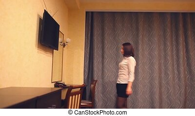 Maid woman administrator on phone in the hotel room at night...