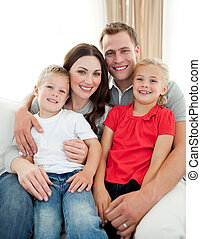 Close-up of adorable family sitting on sofa in the living...