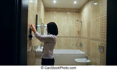 Maid woman makes cleaning bathroom towel straightens - Maid...