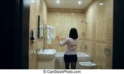 Maid woman makes cleaning the bathroom towel straightens -...