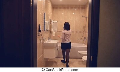 Maid makes woman cleaning bathroom towel straightens - Maid...