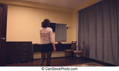 Maid staff woman straightens the chairs in the room at the...