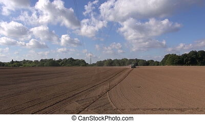 Tractor plowing clay soil field on sunny dry day