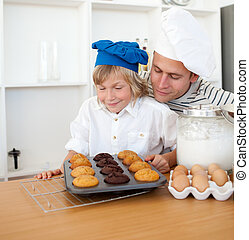 Attentive father and his son presenting their muffins in the...