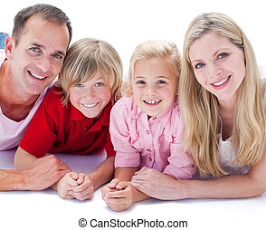 Portrait of family lying on the floor against a white...
