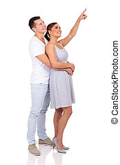 young couple pointing up