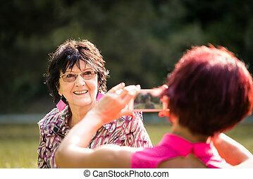 Woman taking photo of her senior mother