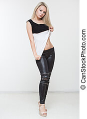 Beautiful girl in black leather pants on a white