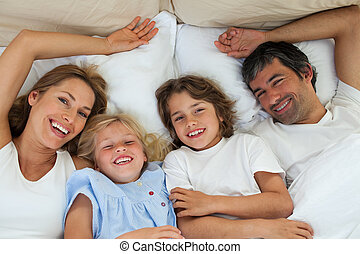 Jolly family relaxing lying on a bed